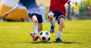 Competencia joven de los jugadores de fútbol Muchachos que golpean la bola del fútbol con el pie Foto de archivo