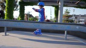 Competencia que se divierte, niño en el rodillo que gana velocidad en el parque del patín almacen de metraje de vídeo