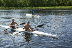 Competencias que se divierten en los kajaks y la canoa imagenes de archivo