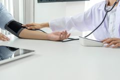 Competent attentive doctor being measuring blood pressure to pat. Ient, hospital and medicine concept royalty free stock image