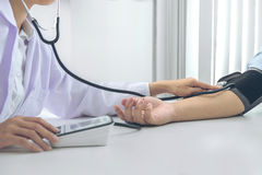 Competent attentive doctor being measuring blood pressure to pat. Ient, hospital and medicine concept stock photography
