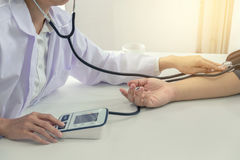 Competent attentive doctor being measuring blood pressure to pat. Ient, hospital and medicine concept stock images