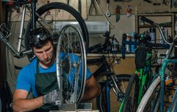 Competent bicycle mechanic in a workshop repairs a bike. Master stock photo