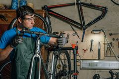 Competent bicycle mechanic in a workshop repairs a bike. Master stock photos