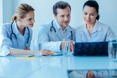 Competent doctor explaining situation to his assistants. Work in team. Smiling females sitting near their colleague and listening to him while examining picture stock images