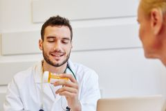 Competent doctor gives medicament to patient. And gives advice Royalty Free Stock Photography