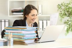 Competent executive working hard. Online with a laptop and a lot of paperwork at office Royalty Free Stock Image