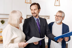 Competent legal advisor presenting contract for aged couple of clients stock image