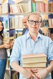 Competent librarian or bookseller. In the library or bookstore stock photos