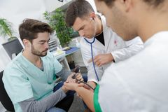 Competent male nurse with doctor. Blood stock photos