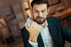 Competent male person looking at his fist. It is boring. Young businessman opening his mouth and raising eyebrows while holding paper ball in right hand stock photography