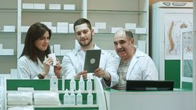 Competent pharmacy team with pharmacist and pharmacy technicians having video chat with colleagues using digital tablet. Professional shot in 4K resolution stock images