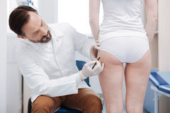 Competent plastic surgeon getting his client ready for forthcoming procedure Royalty Free Stock Images