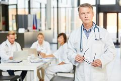 Competent senior physician in front of his clinic team. Man as a competent doctor and senior physician in front of his clinic team in a meeting royalty free stock image