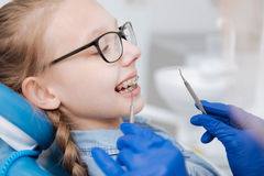 Competent young dentist fixing patients braces Stock Image