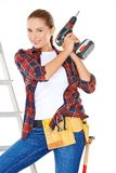 Competent young DIY woman. Competent attractive young DIY woman balancing on a stepladder holder a drill and wearing a tool belt  over white Royalty Free Stock Image