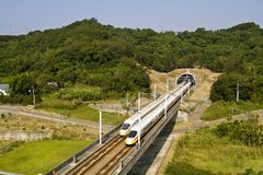 Competetion. High speed commuter train driving across tunnel with mountain scenery Stock Photography