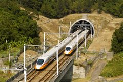 Competetion. High speed commuter train driving across tunnel with mountain scenery Royalty Free Stock Images