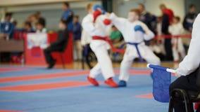 Competições da arte marcial - treinador-juiz com a bandeira azul que olha a luta do ` s do adolescente do karaté Fotos de Stock