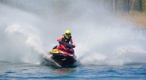 Competidor de Jet Ski que arrincona a la velocidad que crea en la porción de espray Imagen de archivo libre de regalías