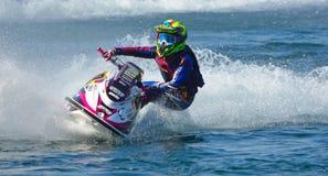 Competidor de Jet Ski que arrincona a la velocidad que crea en la porción de espray Foto de archivo