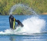 Competidor de Jet Skier del estilo libre que realiza el salto mortal hacia atrás que crea en la porción de espray Fotografía de archivo