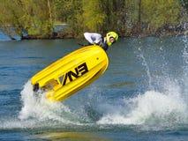Competidor de Jet Skier del estilo libre que realiza el salto mortal hacia atrás que crea en la porción de espray Imagen de archivo