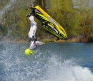 Competidor de Jet Skier del estilo libre que realiza el salto mortal hacia atrás que crea en la porción de espray Imagen de archivo libre de regalías