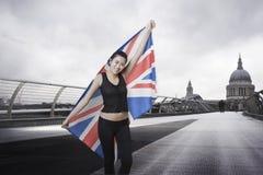 Competidor olímpico con Union Jack delante de la catedral de San Pablo en Londres Fotos de archivo
