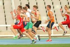 Competidores en el comienzo de el 100m imagen de archivo