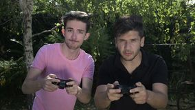 Competidores jovenes enfocados que juegan una competencia del videojuego usando la palanca de mando al aire libre en naturaleza - metrajes
