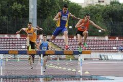 Competidores masculinos en la carrera de obstáculos de los 3000m Imagen de archivo libre de regalías