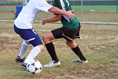 Competing. Two soccer players getting very physical going after the ball royalty free stock photo
