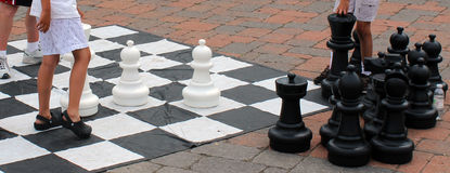 Competing. From the picture we can see that two boys their legs are playing chess on ground, competing each other. It is almost the end of the game, it becomes stock photos