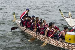 Competing team of people embark on Sports Native Row Boat during Dragon Cup Competition. San Pablo City, Laguna, Philippines - January 9, 2016: Competing team royalty free stock photography
