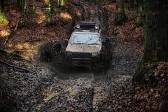 Competir con los coches campo a través SUV cubrió con el fango pegado en suciedad en la trayectoria Imágenes de archivo libres de regalías