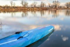 Competir levanta-se o paddleboard em um lago calmo Fotografia de Stock