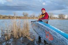 Competir levanta-se o paddleboard em um lago calmo Fotografia de Stock Royalty Free