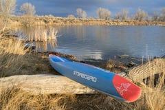 Competir levanta-se o paddleboard em um lago calmo Fotos de Stock