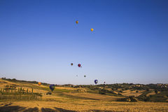 Competition of balloons in Italy. GUALDO CATTANEO, ITALY - JULY 31, 2016: Sagrantino International Challenge Cup. Colorful hot air balloons flying in the sky Royalty Free Stock Photo