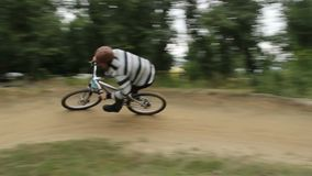 Competition bicycle BMX bikes racer rides difficult track helmet. Stock footage stock footage