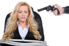 Competition. Business woman bound to a chair with rope and aim it to the head with a gun isolated on a white background Royalty Free Stock Images