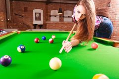 Young woman playing billiard. Competition concept. Young focused girl having fun with billiard. Pretty fashionable woman spending time on playing rivalry Stock Image