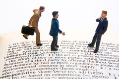 Competition Definition. Miniature businessmen with competition definition Royalty Free Stock Image