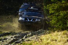 Competition, energy and motorsport concept. Auto racing on fall nature background. Off road vehicles or SUV overcomes. Obstacles. Car racing in autumn forest stock photography