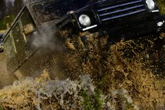 Competition, energy and motorsport concept. Car racing with dirty road. Off road vehicle or SUV crossing puddle with. Dirty water and mud splash, close up stock image