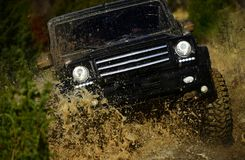 Competition, energy and motorsport concept. Off road vehicle or SUV crossing puddle with dirt splash. Car racing in. Autumn forest. Auto racing on fall nature stock image