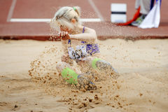 Competition long jump women. Landing in sand a spray Stock Images