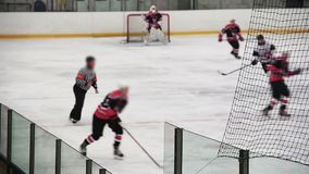 Competition between male hockey teams on ice rink, players defending goal crease. Stock footage stock footage