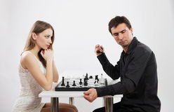 Competition between man and woman, concept. Serious men and women playing chess, light background stock photo